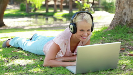 A woman lies in the park with headphones on while listening to a laptop