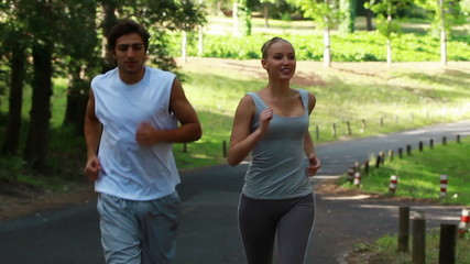 A couple jog together on the road