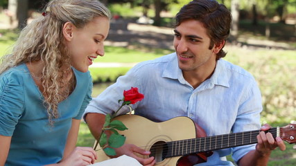 Boyfriend plays guitar for his girlfriend as she holds a rose and then kiss