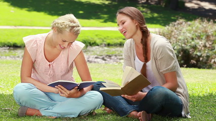 Two ladies reading in the park as they then look at the camera