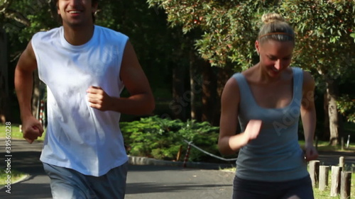 A smiling couple look to one another as they jog