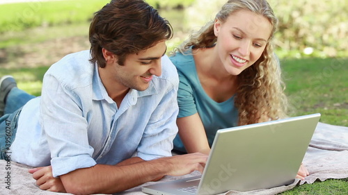 A man lies with a laptop as his girlfriend lies beside him and they look into the camera