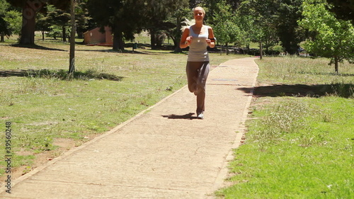 A woman jogs up a footpath past the camera