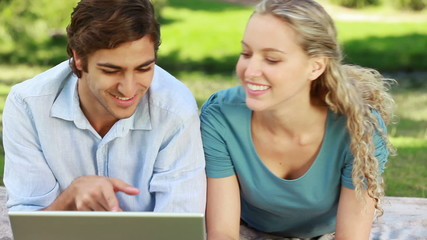 Woman lies down beside her boyfriend as they watch a laptop and then look into the camera