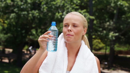 A woman takes a drink of water and then wipes her forehead