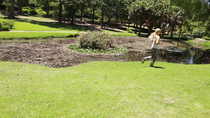 A woman jogs past a pond while the camera pans across with her