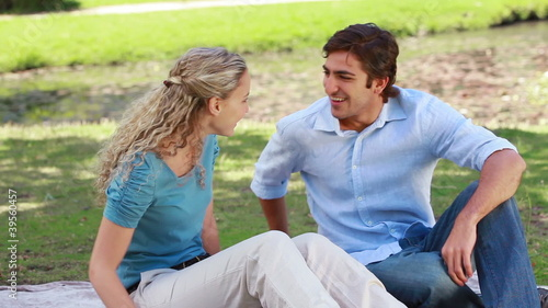 A man sits down beside his girlfriend and gives her a kiss before they talk together