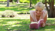 A woman reading a book lying in the park as she then looks at the camera