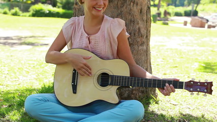 A woman sitting by a tree playing guitar