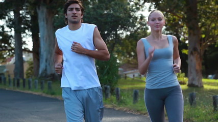 A couple jog together as the camera fades twice to them at different places