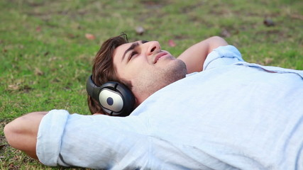A man lies down while listening to music on his headphones