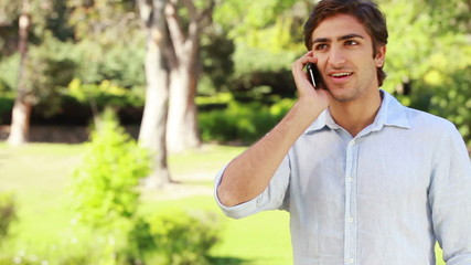 A man talks on the phone and then hangs up and looks into the camera