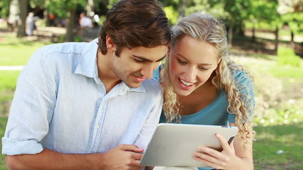 A couple use a tablet together as they then look at the camera