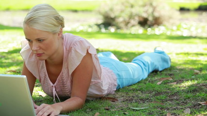A camera pans past a woman lying down and using her laptop