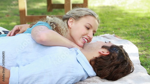 A smiling couple lie together on the ground as they then look at the camera
