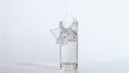 Cube falling in super slow motion breaking the glass