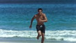 Young man running in slow motion in shorts
