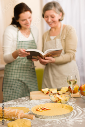 Apple pie recipe two women looking cookbook