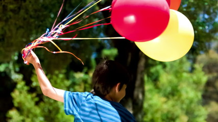 Boy holding balloons in slow motion
