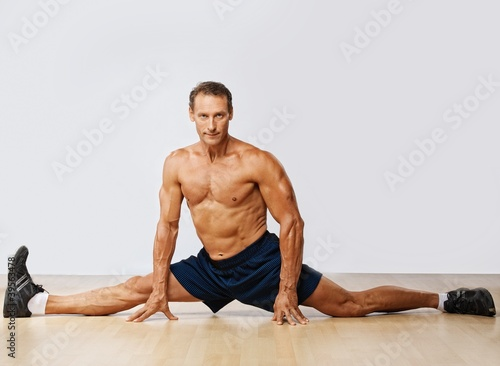 Handsome muscular man doing the splits.