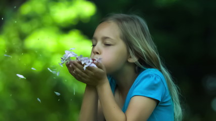Girl in slow motion blowing petals