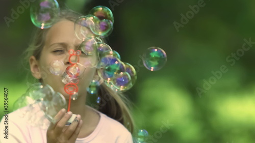 Little girl in slow motion blowing bubbles