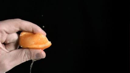 Orange being squeezed in super slow motion