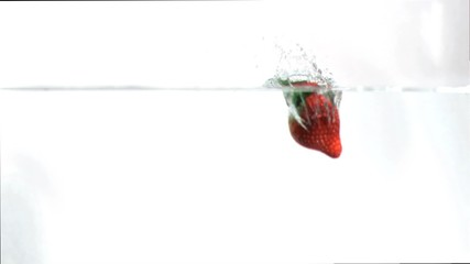 Strawberry falling into water in super slow motion