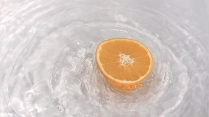 Orange turning in water in super slow motion