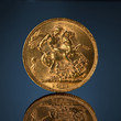 old golden sovereign coin on blue