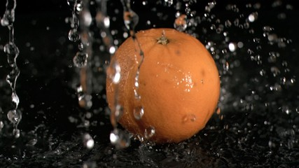 Water raining on orange in super slow motion