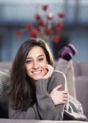 Portrait of a beautiful young woman lying on couch