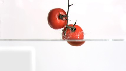 Tomatoes falling into water in super slow motion