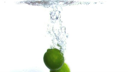 Limes falling into water in super slow motion