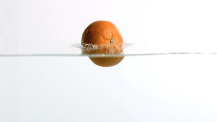 Orange falling into water in super slow motion