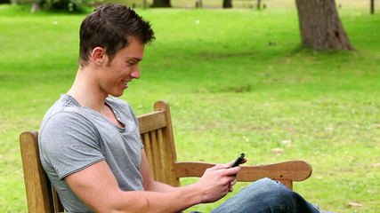 Man laughing as he reads a text message before looking towards the camera and smiling