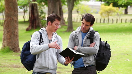 Man using a book to explain something to his friend who has his arms crossed