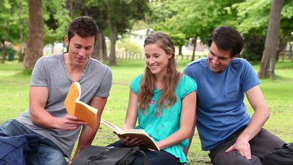 Man shows a book to his friends while smiling as they sit together in a park