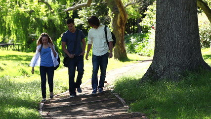 Three friends talking to each other as they walk on a park trail