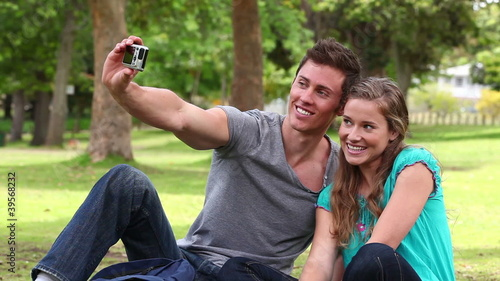 Two friends sitting together before using a camera to take a picture of themselves