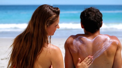Woman applying sunscreen on her boyfriend