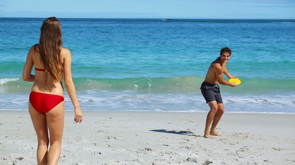 Happy couple playing frisbee