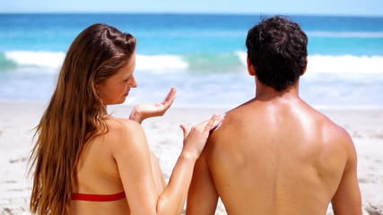 Brunette applying sunscreen on her boyfriend