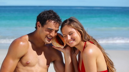 Smiling couple listening to a seashell