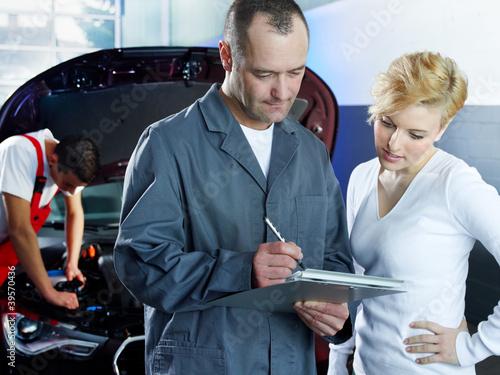 Master mechanic explaining repair costs to customer in garage
