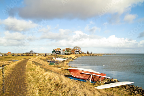 Wide view at the IJsselmeer with traditional houses in the Nethe