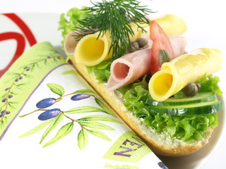 Garnished sandwich on decorative plate and napkin