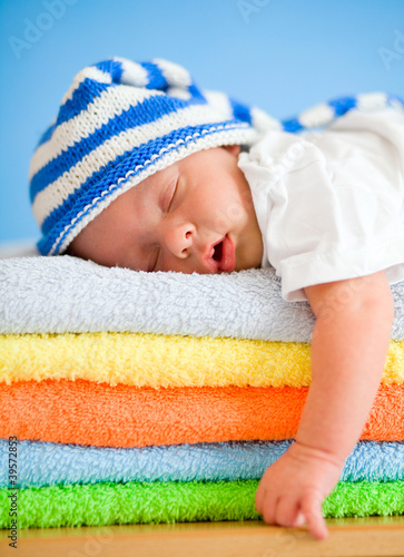Sleeping baby on colorful towels stack - 39572853