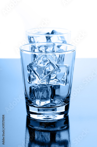 Glasses with crystal clear ice cubes on glossy background