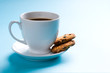 Coffee cup with cookies on blue background
